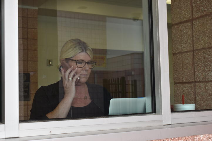woman speaking on cell phone photo taken outside looking through window