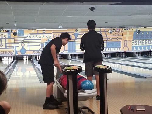 Middle School boys picking up balls at the bowling lanes