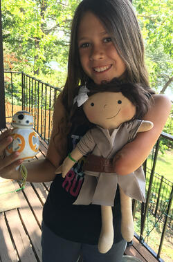 girl who has an amputated arm holds a doll that also is missing an arm
